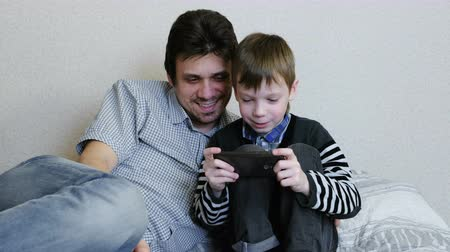 szülő : Dad and son playing game in the mobile phone together.