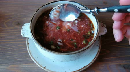 barszcz : Russian national food, red beet soup, borscht. Closeup mans hand with spoon mix sour cream in the soup.