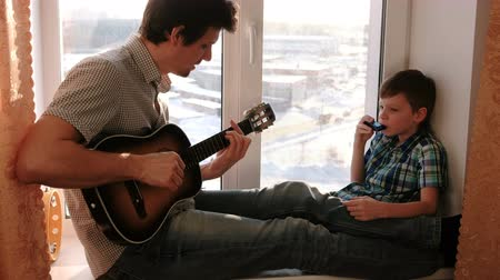 akkord : Playing a musical instrument. Dad is playing the guitar and son is playing mouth organ sitting in windowsill.