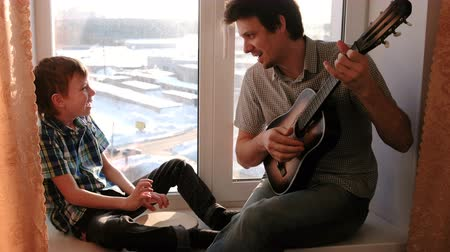 tambourine : Playing a musical instrument. Dad is playing the guitar and son is playing tambourine sitting in windowsill.