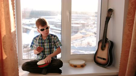tambourine : Playing a musical instrument. Boy plays the drum sitting on the windowsill. Stock Footage