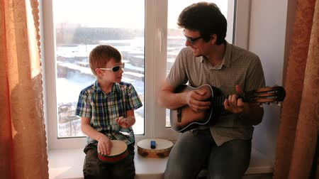 tambourine : Playing a musical instrument in sunglasses. Dad is playing the guitar and son is playing drum sitting in windowsill. Stock Footage