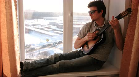 tambourine : Playing a musical instrument. Man in sunglasses is playing the guitar sitting in windowsill. Stock Footage