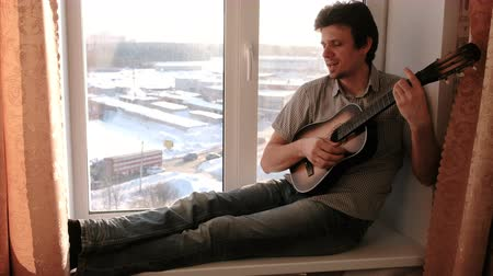 tambourine : Playing a musical instrument. Man is playing the guitar sitting in windowsill. Stock Footage