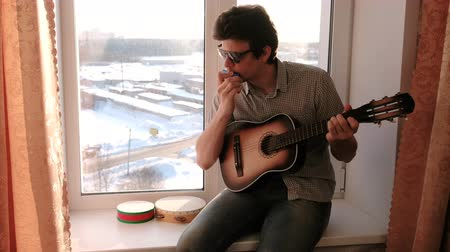 tambourine : Playing a musical instrument. Man is playing the mouth organ sitting in windowsill