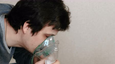 respiratory infection : Use nebulizer and inhaler for the treatment. Young man inhaling through inhaler mask. Side view.