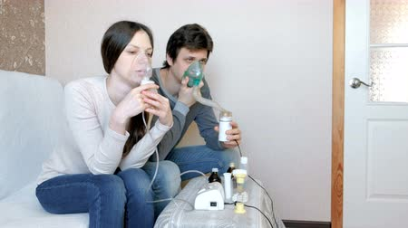 respiratory infection : Use nebulizer and inhaler for the treatment. Man and woman inhaling through inhaler mask. Front view.