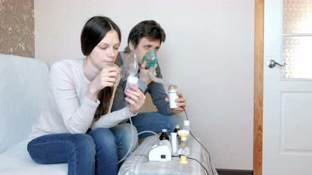 sedative : Use nebulizer and inhaler for the treatment. Man and woman inhaling through inhaler mask. Front view.