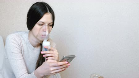 sedative : Use nebulizer and inhaler for the treatment. Young woman inhaling through inhaler mask. Side view. Stock Footage