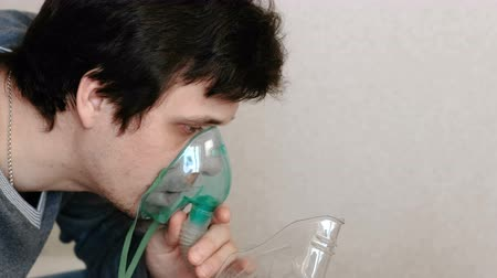sedative : Use nebulizer and inhaler for the treatment. Young man inhaling through inhaler mask. Side view.