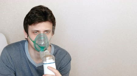 respiratory infection : Use nebulizer and inhaler for the treatment. Young man inhaling through inhaler mask. Front view.