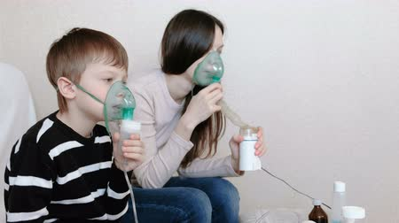 respiratory infection : Use nebulizer and inhaler for the treatment. Woman and boy inhaling through inhaler mask. Side view.