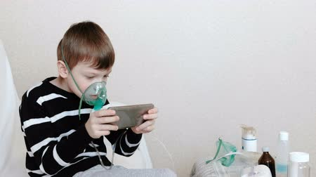 yatıştırıcı : Use nebulizer and inhaler for the treatment. Boy inhaling through inhaler mask and playing the game in his mobile phone. Side view.
