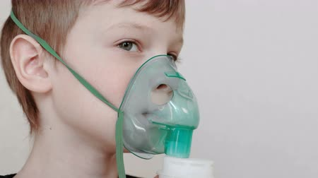 respiratory infection : Use nebulizer and inhaler for the treatment. Boy inhaling through inhaler mask. Front view.