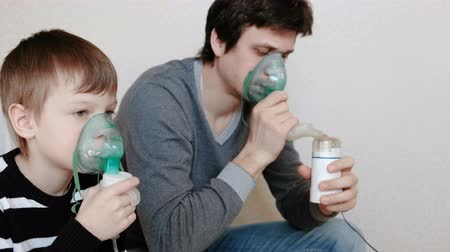 soluma : Use nebulizer and inhaler for the treatment. Man and boy inhaling through inhaler mask. Side view. Stok Video