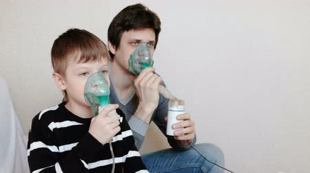 şartlar : Use nebulizer and inhaler for the treatment. Man and boy inhaling through inhaler mask. Side view. Stok Video