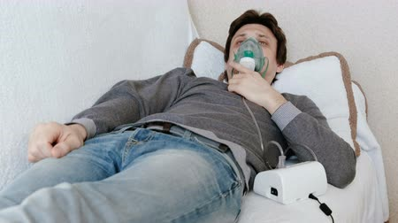 soluma : Use nebulizer and inhaler for the treatment. Young man inhaling through inhaler mask lying on the couch. Front view