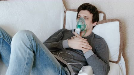 respiratory infection : Use nebulizer and inhaler for the treatment. Young man inhaling through inhaler mask lying on the couch. Front view