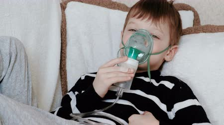 pŁuca : Using nebulizer and inhaler for the treatment. Boy inhaling through inhaler mask lying on the couch.