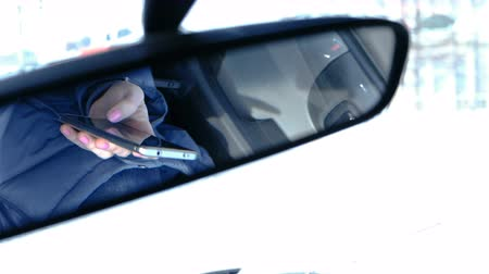 descarregamento : Woman in a car with a mobile phone. Closeup womans hands browsing internet pages in mobile phone. View from rearview mirror.