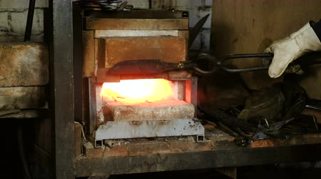 munka : Making the knife out of metal at the forge. Heating of metal billets in the furnace.