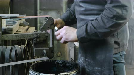 abilities : Grinding billets of metal on a belt-grinding machine. Close-up of a mans hand.