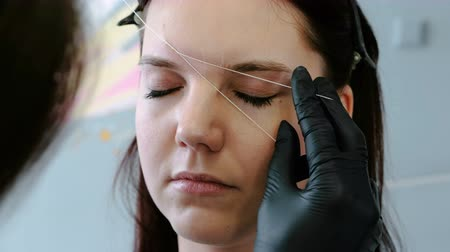 tweezing : Cosmetologist performs the procedure of correction eyebrow threading. Front view.