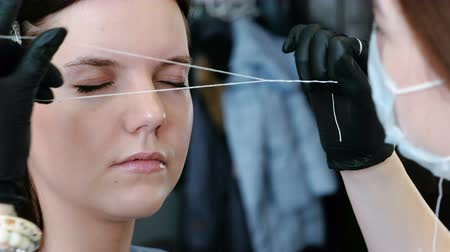 tweezing : Cosmetologist performs the procedure of correction eyebrow threading. Side view.
