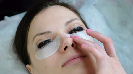 laminação : Beauty treatment. Closeup womans face with paint on eyelashes. Botox and laminating eyelashes. Top view. Vídeos