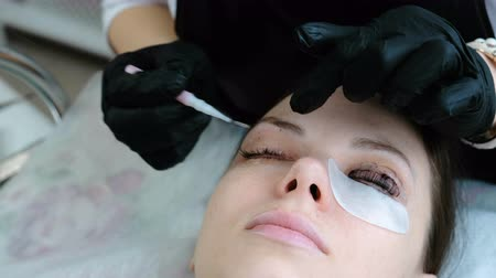 деление : Beautician removes paint from the eyes of the client with brush. Botox and lash lamination. Стоковые видеозаписи