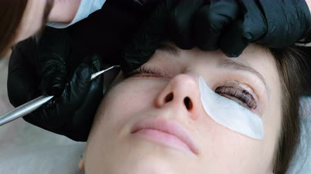 деление : Beautician separates the lashes with a needle. Botox and lash lamination. Beauty treatment.