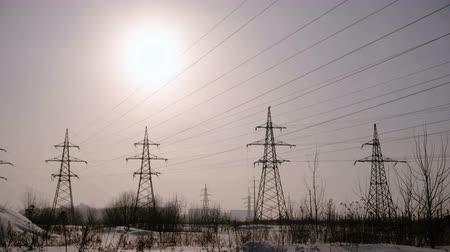 továbbít : High-voltage towers, transmission line in winter city background.