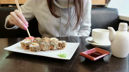 california rolls : Woman takes wasabi and ginger by wooden sticksand puts it on a roll. Dips roll into soy sauce. Stock Footage
