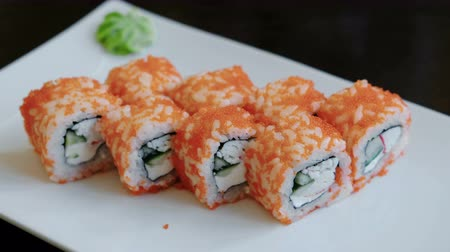 california rolls : Close-up rolls with caviar with pickled ginger and wasabi on a white rectangular plate. Stock Footage