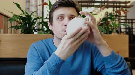 travessura : Young man brunette look at teapot and drink from the spout and frown. Front view. Vídeos
