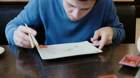 travessura : Young man brunette eats the crumbs from the plate and licks the plate with tongue.