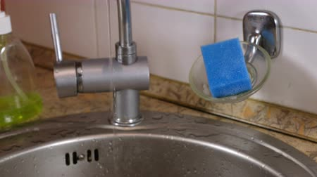 vazamento : Water flows in a thin stream from the tap in the kitchen. Broken faucet.