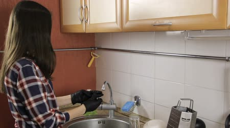 colocando : Brunette with long hair in a plaid shirt takes off rubber gloves.