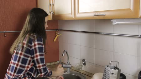 oppression : Brunette with long hair in a plaid shirt clears congestion in the sink with the plunger.