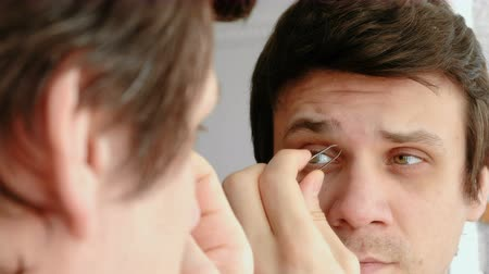 pinça : Young man plucking his eyebrows with tweezers. Styling eyebrows.