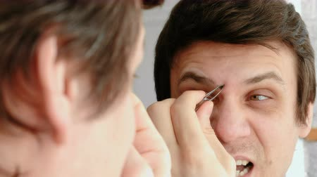 pinça : Young man plucking his eyebrows with tweezers and and winces from the pain. Styling eyebrows. Vídeos