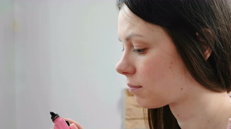 imagem : Woman removes the excess mascara from the brush to paint the eyes.