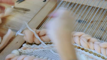 pigtail : Weaving on a loom. Weaving on a loom. Closeup womans hands running on a loom. Threading the needle through the strands of frame