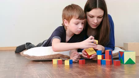 logic : Mom and son playing together wooden colored education toy blocks lying on the floor.