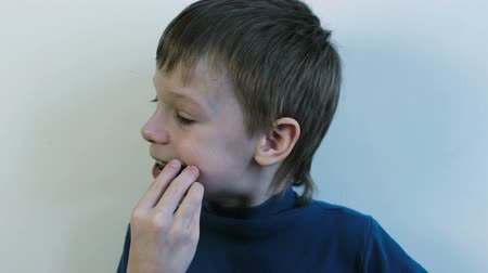 жевать : Boy eats too much sweets. Seven-year-old boy eats a delicious chocolate bar and licks stained fingers.