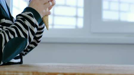 amostra : Boys hands takes Ice cream in a horn from the kitchen table and eat it. Unrecognizable boy in stripes jacket.