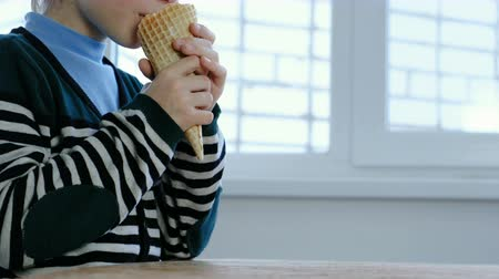 сладость : Unrecognizable boy in stripes jacket eats Ice cream in a horn at home.