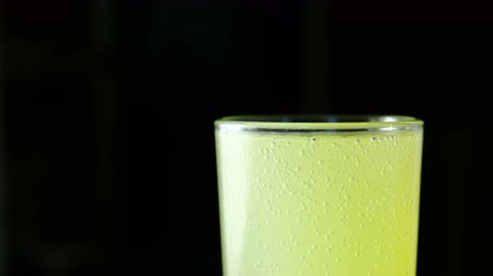 fışırdamak : Closeup half of full glass with carbonated yellow drink on a black background. Stok Video