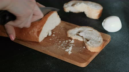 picado : Closeup womans hands cutting a piece of white bread on wooden board in black background. Making a sandwich. Stock Footage