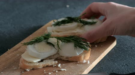 assar : Closeup womans hand takes a sandwich with bread, butter, eggs and dill from wooden board in black background.